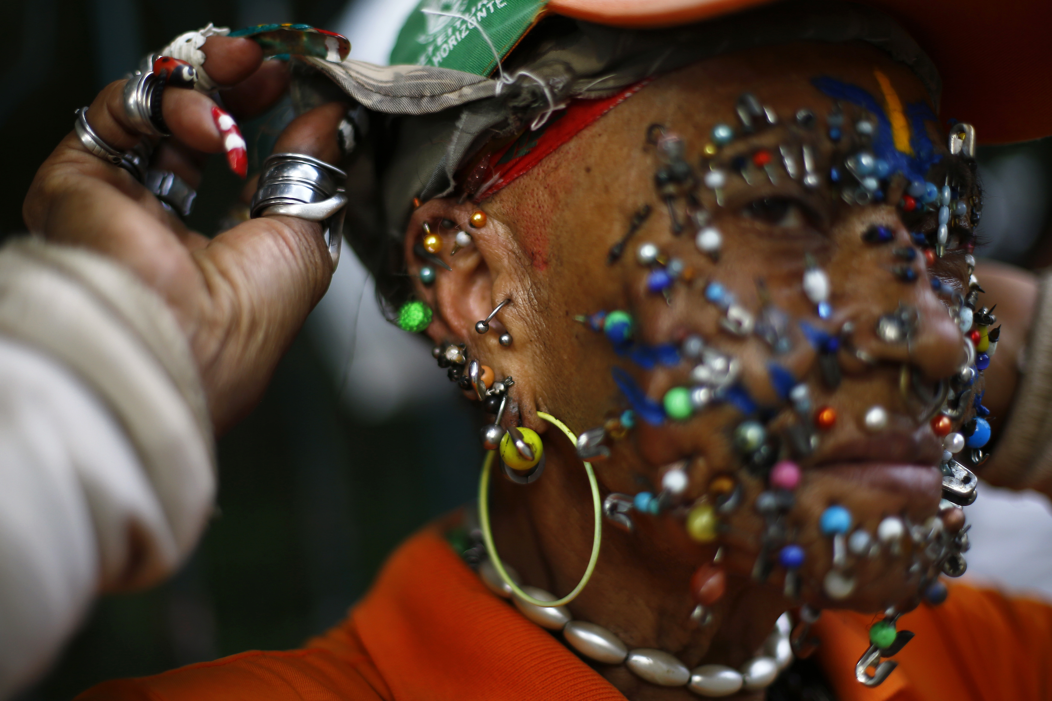 A street cleaner and fan of the Brazilian national soccer team shows her facial piercings on a street in Belo Horizonte